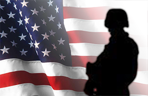 Solider silhoutted in front of US flag